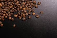 R?stkaffeebohnen in der Masse auf einem schwarzen Hintergrund dunkles cofee briet Kornaroma-Aromacaf?, den nat?rlichen coffe Gesc stockfoto