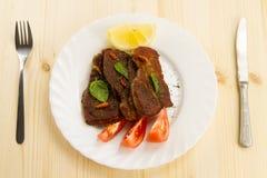 Rôti de porc du plat blanc sur le fond en bois avec des légumes photographie stock