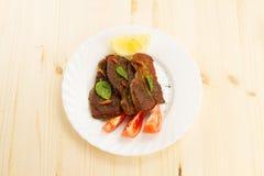 Rôti de porc du plat blanc sur le fond en bois avec des légumes images stock