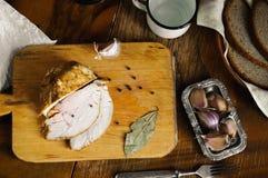 Rôtissez la viande de dinde avec la feuille de laurier, le poivre et l'ail sur la vieille planche à découper, table de pays de vi Image stock