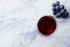 R?tt vin i exponeringsglas med den nya druvan p? marmortabellbakgrund Top besk?dar kopiera avst?nd arkivfoto