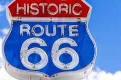 R?tt, vitt och bl?tt Route 66 tecken som ?r fr?mst av bl? himmel royaltyfri fotografi