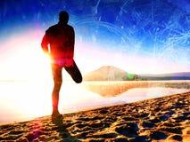 r Uomo che si esercita sulla spiaggia Siluetta dell'uomo attivo che si esercita e che allunga sulla spiaggia del lago all'alba Fotografia Stock Libera da Diritti