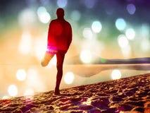 r Uomo che si esercita sulla spiaggia Siluetta dell'uomo attivo che si esercita e che allunga sulla spiaggia del lago all'alba Immagine Stock Libera da Diritti