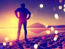 r Uomo che si esercita sulla spiaggia Siluetta dell'uomo attivo che si esercita e che allunga sulla spiaggia del lago all'alba Fotografie Stock