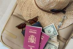 r Valigia con il cappello femminile, gli occhiali da sole, i passaporti spagnoli, i dollari ed il lucchetto Immagine Stock