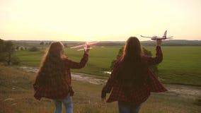 R?ves du vol concept d'enfance heureux Deux filles jouent avec un avion de jouet au coucher du soleil Enfants sur le fond du sole clips vidéos