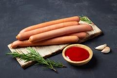 R? wienerkorvkorvar med ketchup p? sk?rbr?da fotografering för bildbyråer