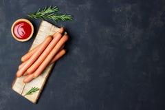 R? wienerkorvkorvar med ketchup p? sk?rbr?da royaltyfria bilder