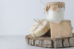 r Zusammenstellung von traditionellen Arten des Käses auf hölzernem Schneidebrett gegen weiße Wand stockfotografie