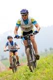 Raça através dos campos de bicicleta de montanha Fotografia de Stock