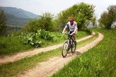 Raça através dos campos de bicicleta de montanha Foto de Stock
