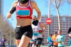 Raça running da maratona, corredor da mulher na estrada Fotos de Stock Royalty Free