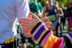 Raça running da maratona, corredores do apoio na estrada, doação da mão da criança highfive Fotografia de Stock Royalty Free