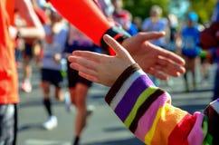 Raça running da maratona, corredores do apoio na estrada, doação da mão da criança highfive Imagens de Stock Royalty Free