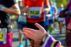 Raça running da maratona, corredores do apoio na estrada, doação da mão da criança highfive Imagem de Stock Royalty Free