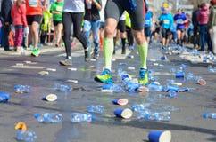 A raça running da maratona, os pés dos corredores e os copos plásticos da água na estrada perto do rafrescamento apontam, ostenta Imagem de Stock