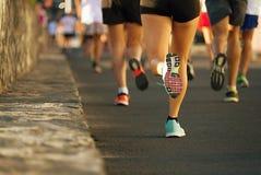 Raça running da maratona, pés dos corredores na estrada Imagens de Stock Royalty Free