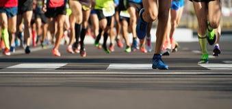 Raça running da maratona, pés dos corredores na estrada Fotografia de Stock Royalty Free