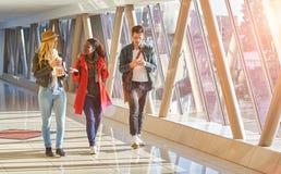3 raças misturadas novas de grupo dos empresários ou de estudantes dos adultos walkin Imagem de Stock