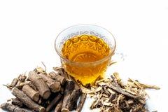 Raíz de regaliz famosa de la hierba o raíz de regaliz o raíz de Mulethi aislada en blanco junto con su té beneficioso en una taza fotos de archivo libres de regalías