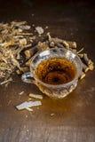 Raíz de regaliz famosa de la hierba o raíz de regaliz o raíz de Mulethi en superficie de madera junto con su té beneficioso en un fotografía de archivo
