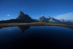 Ra Gusela reflekterar sig över lite den alpina sjön i Dolomites Arkivfoton