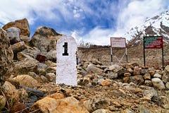 1ra piedra del kilómetro en las montañas de Himalaya Imagenes de archivo
