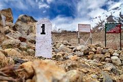 1ra piedra del kilómetro en las montañas de Himalaya Fotos de archivo