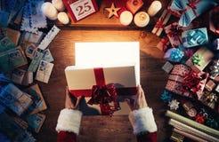 ra Santa che apre un contenitore di regalo Immagine Stock Libera da Diritti