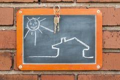 Raad op een bakstenen muur met een huis, sleutels en zon stock afbeeldingen