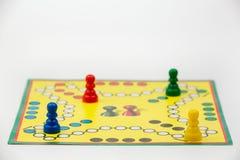 Raadsspel met verschillende gekleurde spelpanden op het Ludo of Droevige het spelcijfers van het raadsspel Stock Afbeeldingen