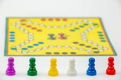Raadsspel met verschillende gekleurde spelpanden op het Ludo of Droevige het spelcijfers van het raadsspel Stock Foto