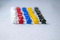 Raadsspelen, happines, kinderen, vrije tijdsconcept Groepen kleurrijke meeples in teams die op grijze achtergrond worden geïsolee royalty-vrije stock fotografie