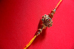 Raakhi auf rotem Hintergrund Stockbild