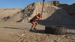 Raakt de strongman mens van de spieratleet een hamer op een reusachtig wiel in de zandige bergen in langzame motie bij zonsonderg stock videobeelden