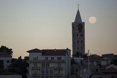 Rab-Stadt an der Dämmerung mit einem hinaufkletternden Vollmond Stockfotos