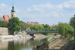 Raba River in Gyor City. Raba River with Carmelite Church Next to the Raba River Bank in Gyor City Royalty Free Stock Images