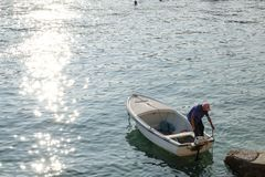 Rabac, Croatia, elderly fisherman with his boat. Croatia, a man with a boat makes maintenance in the port of Rabac stock photos