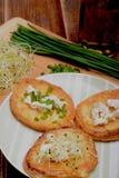 Rabanadas com queijo de cabras, o cebolinha fresco e os brotos Imagem de Stock