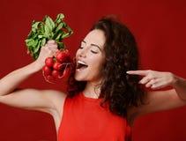 Rabanete fresco da posse nova consideravelmente alegre da mulher do esporte com folhas do verde e dedo apontar dieting Imagens de Stock