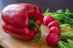 Rabanetes ao redor da pimenta doce vermelha nas gotas Fotografia de Stock Royalty Free