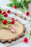 Rabanetes cortados em uma placa de corte de madeira em uma tabela branca imagens de stock royalty free