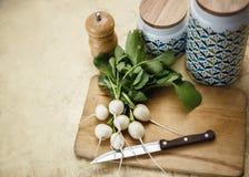 Rabanetes orgânicos frescos incomuns brancos com os dispositivos de cozinha na placa de corte de madeira Foto de Stock