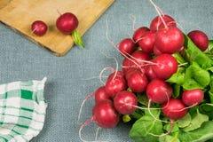 Rabanetes vermelhos frescos no fundo cinzento, na placa de madeira e na toalha de prato fotografia de stock