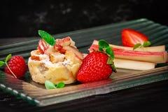 Rabarberkaka med jordgubben på sikt för sida för exponeringsglasplatta arkivfoto