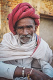 Rabari tribesman. GODWAR REGION, INDIA - 14 FEBRUARY 2015: Elderly Rabari tribesman with red turban and blanket around the shoulders. Post-processed with grain Royalty Free Stock Photos