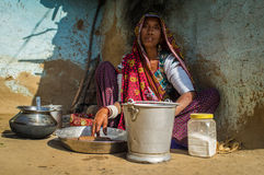 Rabari tribeswoman. GODWAR REGION, INDIA - 13 FEBRUARY 2015: Rabari tribeswoman in sari decorated with traditional upper-arm bracelets cleans dishes. Rabari or Stock Photo