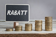 Rabatt discount in German language. White chalk type on black board, Euro money coin stacks of growth on wood table Royalty Free Stock Image