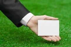 Rabatte und Geschäftsthema: übergeben Sie in einem schwarzen Anzug, der eine weiße leere Karte auf Hintergrund des grünen Grases  Stockbild